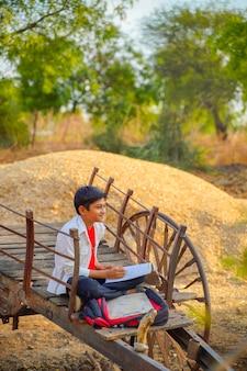 Indische / aziatische schooljongen met notaboek en het bestuderen