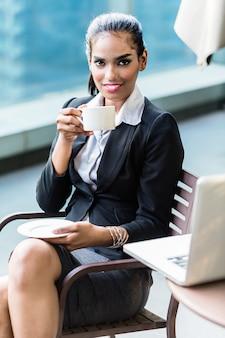 Indische bedrijfsvrouw het drinken koffie die onderbreking heeft