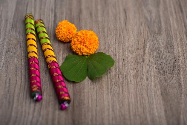Indische festival dussehra en navratriand-goudsbloembloemen met dandiya-stokken op een houten achtergrond