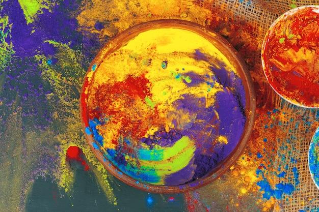 Indische holi-festivalkleuren in kleine kommen op donkere achtergrond
