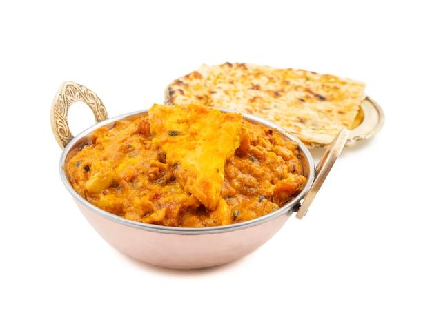 Indische keuken zoete en kruidige paneer pasanda die met knoflook naan op witte achtergrond wordt gediend
