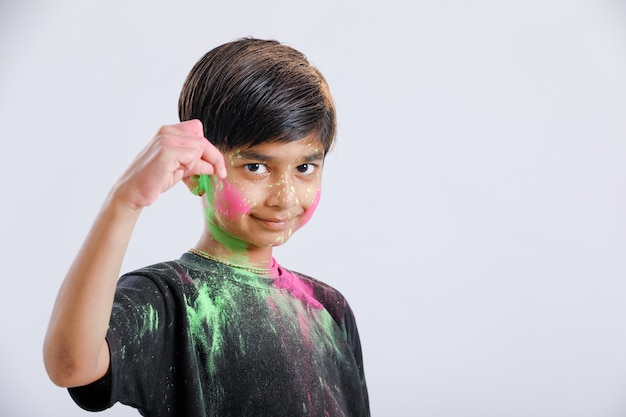 Indische kleine jongen die met de kleur in holifestival speelt