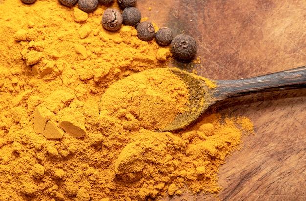Indische kurkuma of kurkuma met peper en lepel op houten tafel
