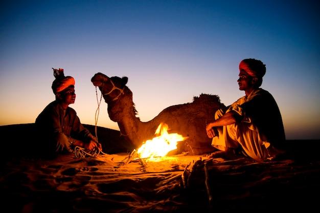 Indische mannen die door het vuur met hun kameel rusten