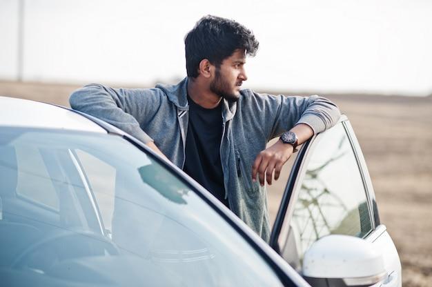 Indische mens bij vrijetijdskleding die dichtbij witte auto wordt gesteld.