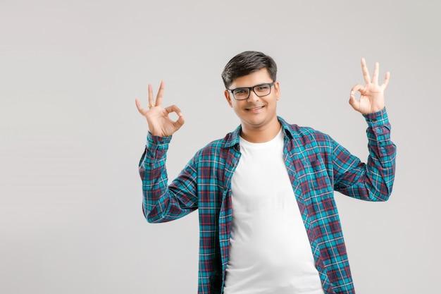Indische mens die gebaar met hand toont, dat over witte achtergrond wordt geïsoleerd