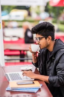 Indische mens die laptop met behulp van terwijl het drinken van een kopkoffie in een openluchtstraatkoffie