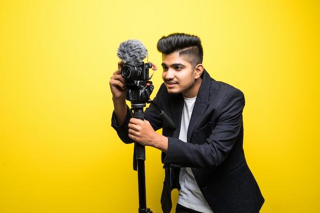 Indische professionele cameraman die op gebeurtenis behandelen met een video die op gele achtergrond wordt geïsoleerd