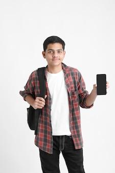 Indische student die het mobiele scherm op witte muur toont