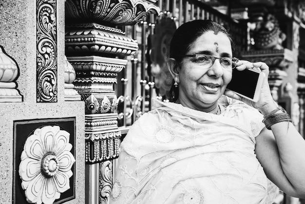Indische vrouw die mobiele telefoon met behulp van