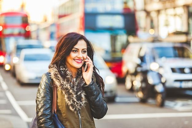Indische vrouw die op de telefoon in londen spreekt