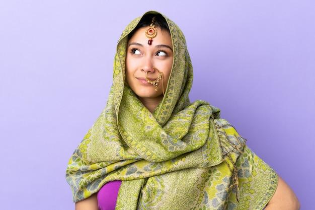 Indische vrouw die op purpere muur een idee denkt terwijl omhoog het kijken