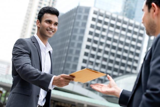 Indische zakenman die document in de envelop geeft aan zijn partner
