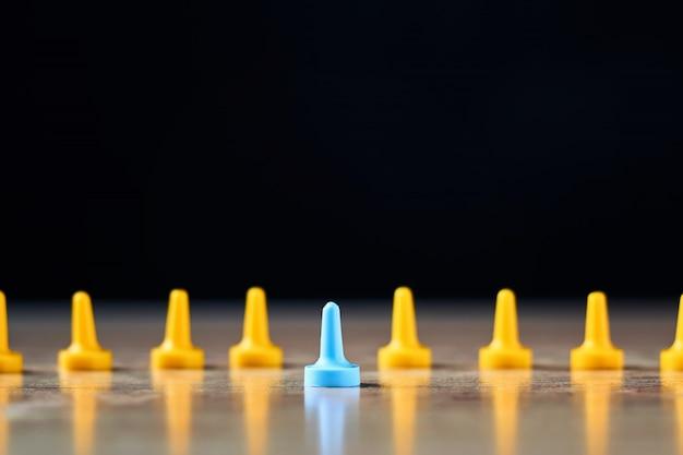 Individualiteit en leiderschap. blauwe figuur opvallend uit gele figuren