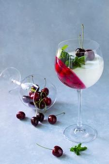 Individueel dessert in wijnglas met kersen. panna cotta met bessen in glas op grijs.