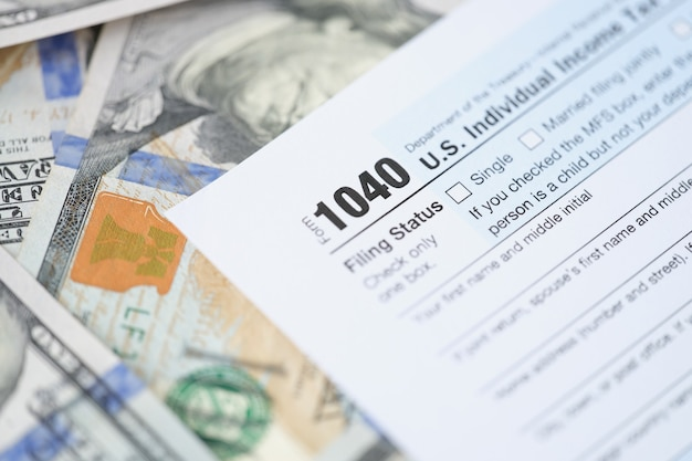 Individuele belastingaangifteformulier en dollars liggen op tafel om jaarlijkse degradatie van inkomen in te dienen