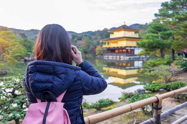 Individuele vrouwelijke toerist die foto's maakt met de camera in de kinkakuji-tempel of het gouden paviljoen in het herfstseizoen, aziatische reizigersbezoek in kyoto, japan. vakantie, bestemming en reisconcept