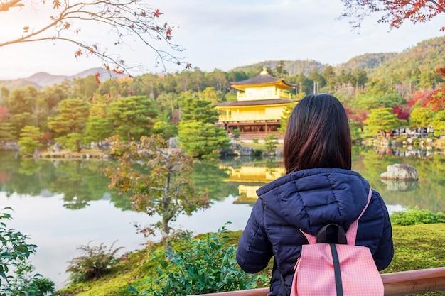 Individuele vrouwelijke toerist die in de kinkakuji-tempel of het gouden paviljoen in het herfstseizoen reist, bezoek van aziatische reizigers in kyoto, japan. vakantie, bestemming en reisconcept