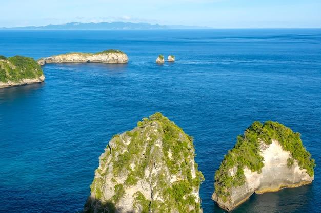 Indonesië. een paar rotsachtige eilandjes met jungle. bergen en wolken aan de horizon