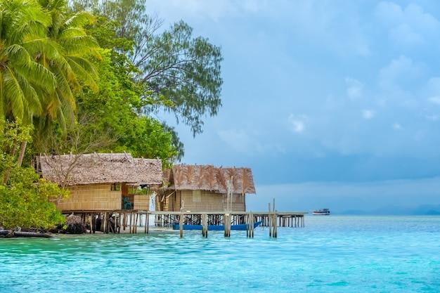 Indonesië. een tropisch eiland bedekt met jungle. bewolkte avond. paalhutten in het water. jacht in de verte