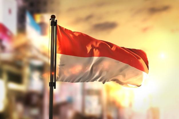 Indonesië vlag tegen stad wazige achtergrond bij zonsopgang achtergrondverlichting