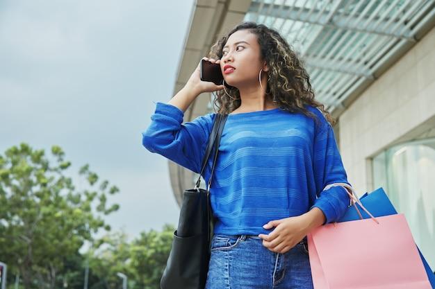 Indonesisch wijfje dat op telefoon tijdens het winkelen spreekt
