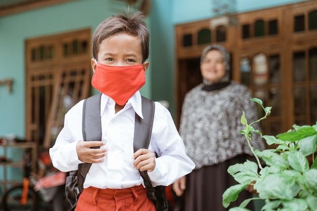 Indonesische aziatische basisschoolleerling die maskers draagt alvorens naar school te gaan