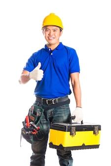 Indonesische aziatische bouwer of bouwvakker met helm en gereedschapsriem zittend op gereedschapskist