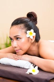 Indonesische aziatische vrouw die in wellness beauty day spa ontspannen kijkt