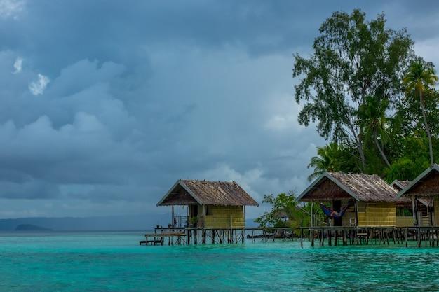 Indonesische eilanden. bewolkte avond. kust van de oceaan en de jungle. hutten op palen in het water