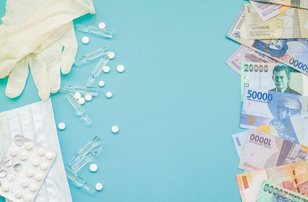 Indonesische roepia geld en tabletten, ampullen met medicijnen, masker