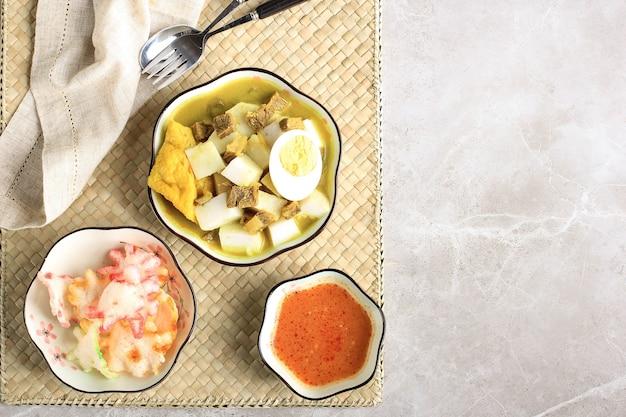 Indonesische traditionele keuken: lontong kari sapi, rijstcake of ketupat geserveerd met rundvleescurrysoep gemaakt van runderbouillon en lichte kokosmelk, verschillende specerijen en indonesische kruiden