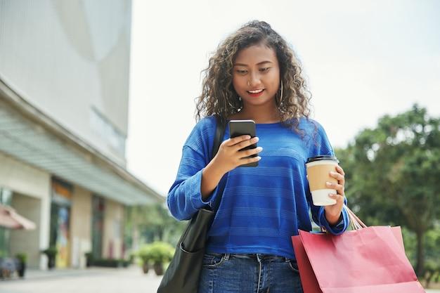 Indonesische vrouw die smartphone gebruikt tijdens het winkelen