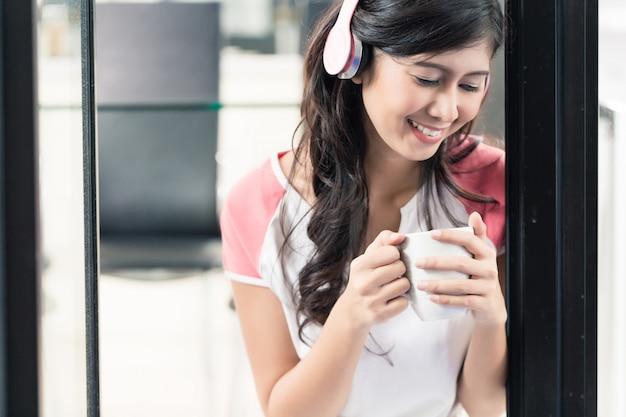 Indonesische vrouw die van muziek thuis met koffie geniet