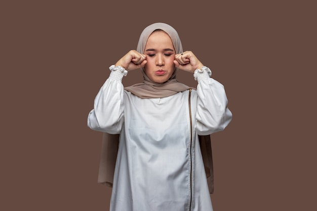Indonesische vrouw hijab poseren huilen en droevige uitdrukking geïsoleerd op effen achtergrond