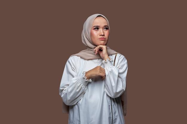 Indonesische vrouw in hijab met droevige, bezorgde en teleurgestelde uitdrukking