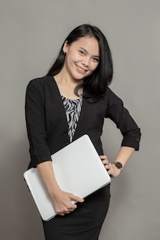 Indonesische vrouw in pak poseren met laptop in de hand