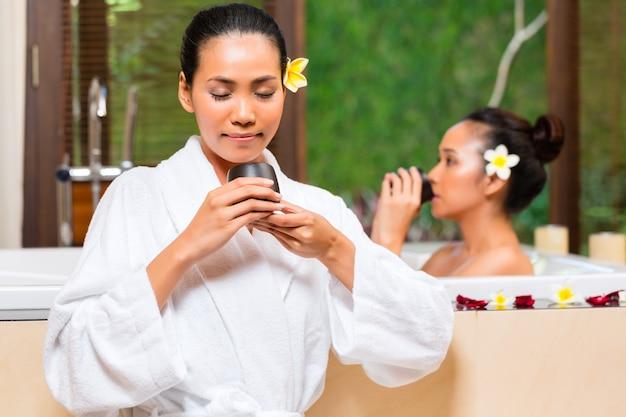 Indonesische vrouwen die wellnessbad hebben die thee drinken