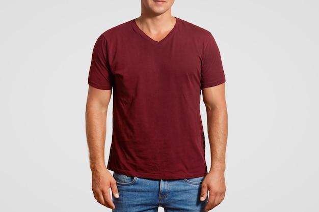 Indoor bijgesneden afbeelding van gespierde jonge man in rode t-shirt en spijkerbroek