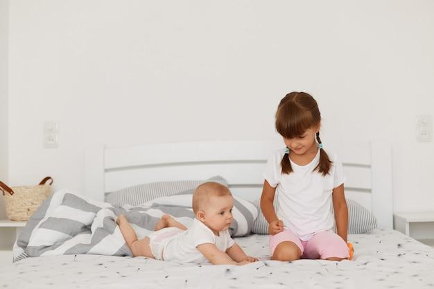 Indoor charmante baby meisje liggend op de buik met witte bodysuit, oudere donkerharige zus met staartjes zitten en kijken naar schattige baby, gelukkige jeugd.