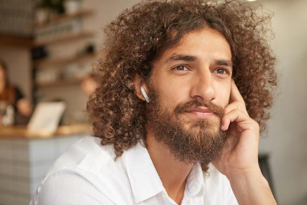 Indoor close-up met knappe jonge man met baard en bruine ogen, zittend in café en luisteren naar muziek, leunend op zijn wang en bedachtzaam naar raam kijken