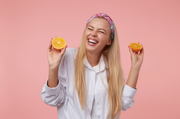 Indoor close-up met mooie jonge blonde vrouw lachend met gesloten ogen en met gesneden sinaasappel in haar handen, staande