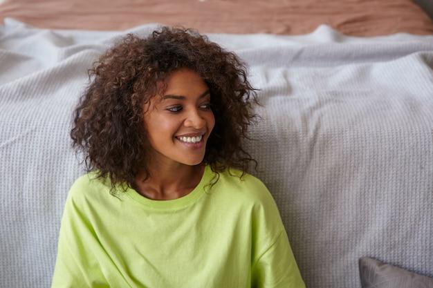 Indoor close-up van gelukkig donkere huid jonge vrouw draagt geel t-shirt, poseren over gezellig interieur, opzij kijken met charmante glimlach