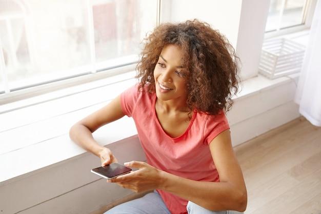 Indoor close-up van mooie jonge krullende vrouw met donkere huid, smarphope in de hand houden en vooruit kijken met een aangename glimlach, roze t-shirt dragen