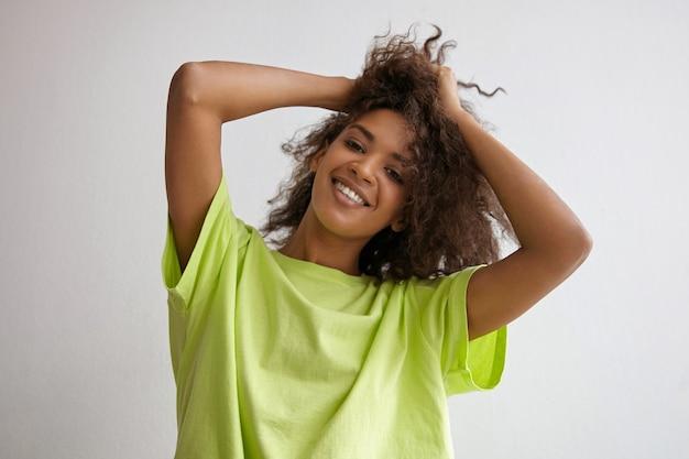 Indoor close-up van positieve donkere huid jonge vrouw die haar haar met handen houdt, op zoek met charmante glimlach, gele t-shirt draagt