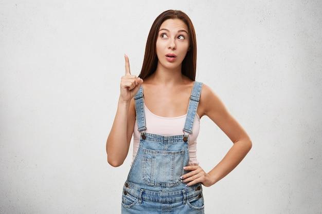 Indoor foto van aantrekkelijke jonge brunette vrouw van europese uitstraling wegkijken en wijsvinger opheffen, met helder idee of interessante gedachte, permanent geïsoleerd op witte muur