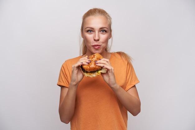 Indoor foto van aantrekkelijke jonge hongerige blonde dame met paardenstaart kapsel heerlijke hamburger kauwen en opgewonden kijken naar camera, gekleed in oranje t-shirt op witte achtergrond