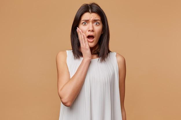 Indoor foto van bange vrouw in paniek nerveus bang, gekleed in witte jurk, houdt hand bij wang geopende mond als feals angst, geïsoleerd