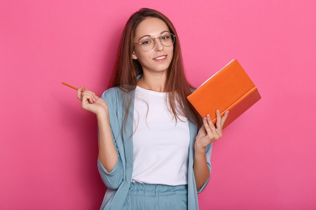 Indoor foto van emotionele vrolijke jonge dame met notebook en pen in beide handen
