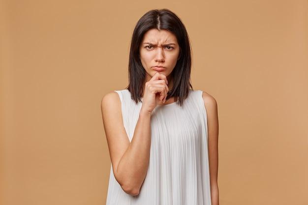 Indoor foto van ernstige verdachte latino vrouw met krullend afro haar staande met gekruiste handen en fronsend, wantrouwend en teleurgesteld,